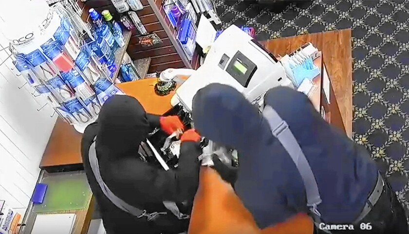 Surveillance footage from Hill Pharmacy on Avocado Avenue in Newport Beach shows two masked burglars taking money from a cash box. The business was one of three pharmacies burglarized in Newport Beach on March 10.