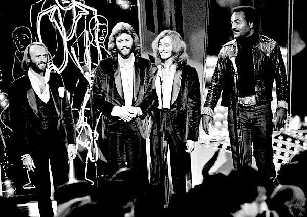 """The Bee Gees, from left, Maurice, Barry and Robin Gibb, join actor Jim Brown, right, on Stage 14 of Paramount Studios during a disco party for the premiere of """"Saturday Night Fever"""" in Los Angeles on Wednesday, Dec. 8, 1977."""