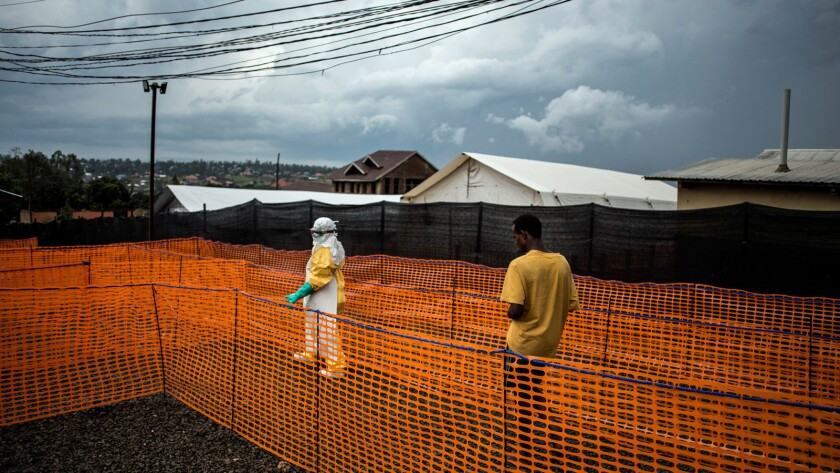 A health worker escorts an unconfirmed Ebola patient to his room this month at a Doctors Without Borders treatment center in Bunia, Congo.