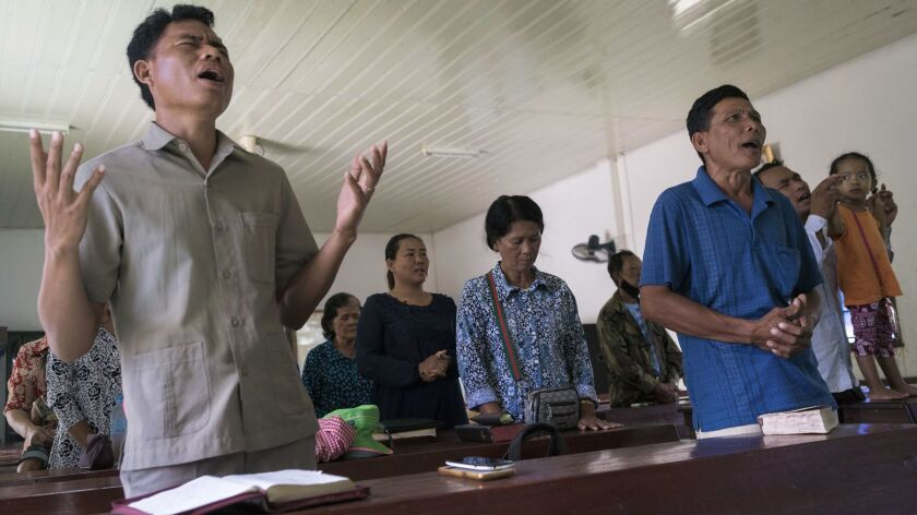 Norng Chhay, right, in blue shirt, participates in a Sunday service at the Pailin's B.P. Presbyterian Church. Norng was a Khmer Rouge soldier for almost 20 years. He converted to Christianity in 2000.