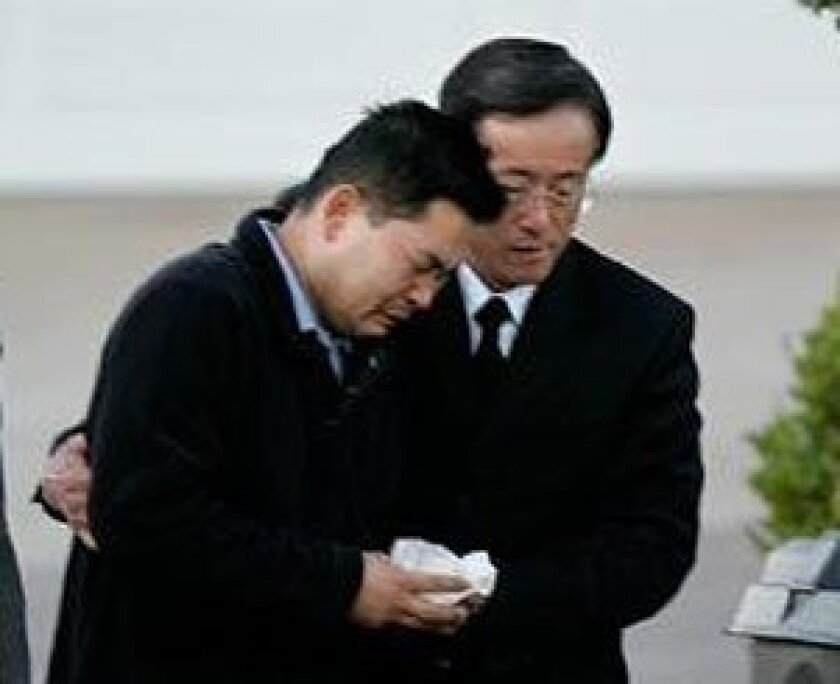 Don Yoon (left) and his minister, the Rev. Daniel Shin arrived at the remains of the Yoon home after the crash that claimed the lives of Yoon's wife, children and mother-in-law.