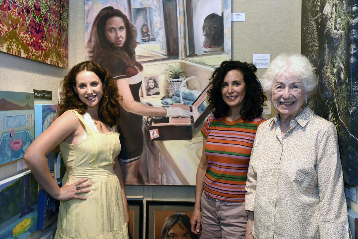 Artist Rachel Greenstein poses by her self-portrait with mom Carrie Greenstein and Grandmother Inge Feinswog