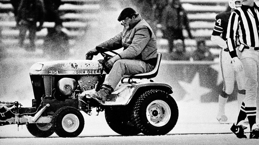 Mark Henderson drives a small tractor fitted with a snow sweeper onto the field at Schaefer Stadium during the third quarter of the New England Patriots' win over the Miami Dolphins on Dec. 12, 1982.