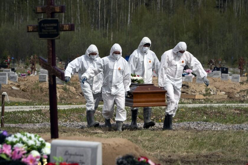 Gravediggers in protective suits carry the coffin of a COVID-19 victim in a cemetery in Kolpino, Russia.