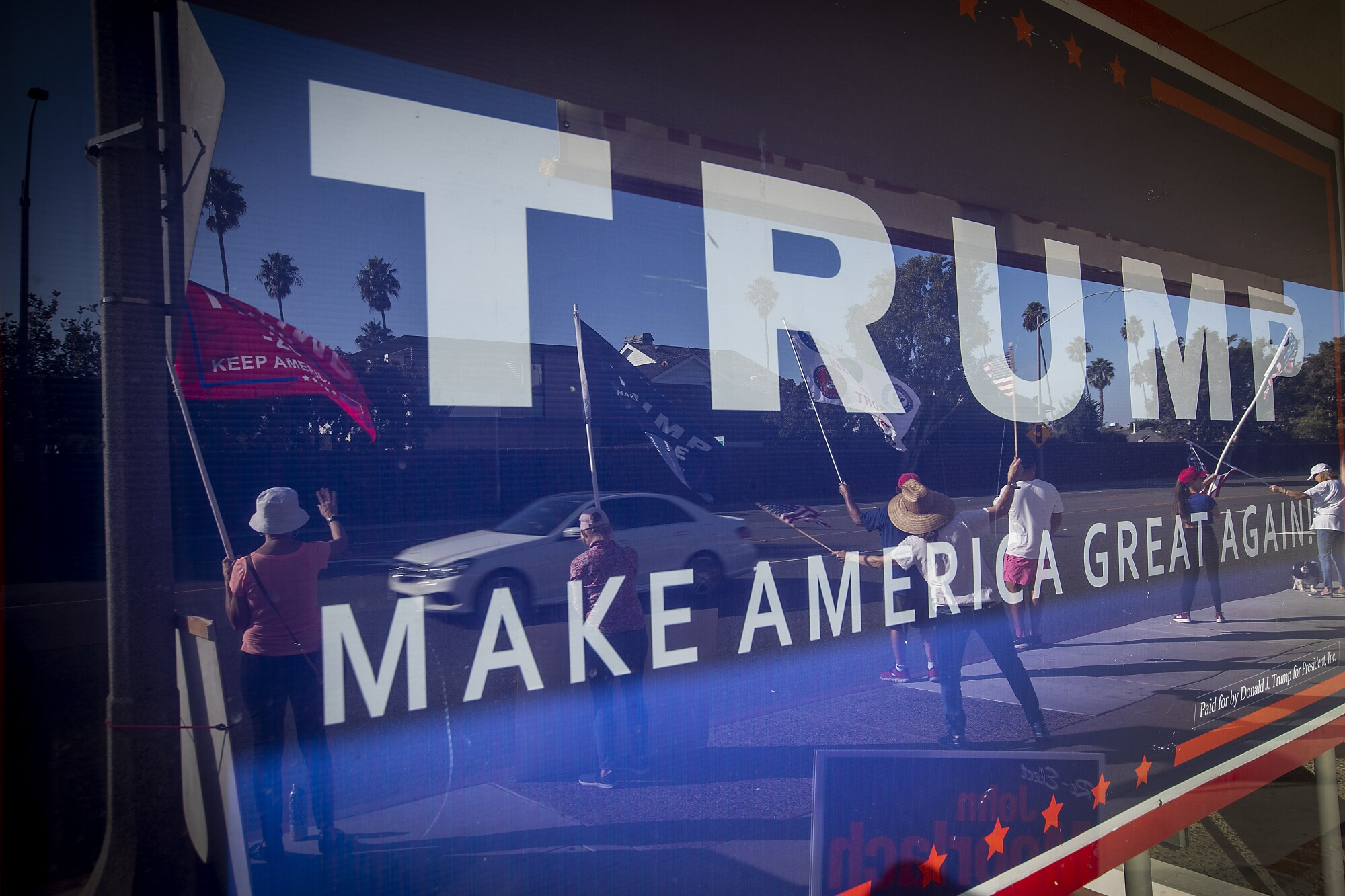 Supporters of President Trump wave to motorists outside Republican Party headquarters in Newport Beach.