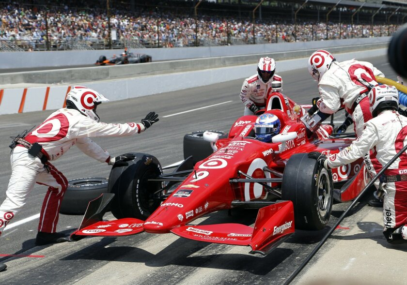 Scott Dixon, of New Zealand, makes a pit stop during the 99th running of the Indianapolis 500 auto race at Indianapolis Motor Speedway in Indianapolis, Sunday, May 24, 2015. (AP Photo/Sam Riche)