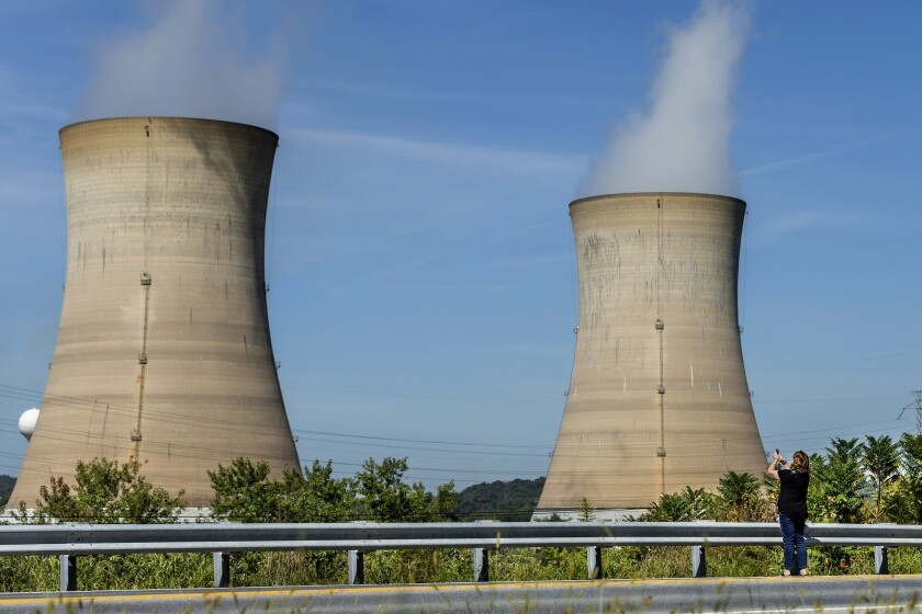 Eileen DeFrancisco, of Middletown, shoots a video of Three Mile Island, site of the United States' worst commercial nuclear power accident, minutes before the power plant was shut down on Friday, Sept. 20, 2019, in Harrisburg, Pa. (Joe Hermitt/The Patriot-News via AP)