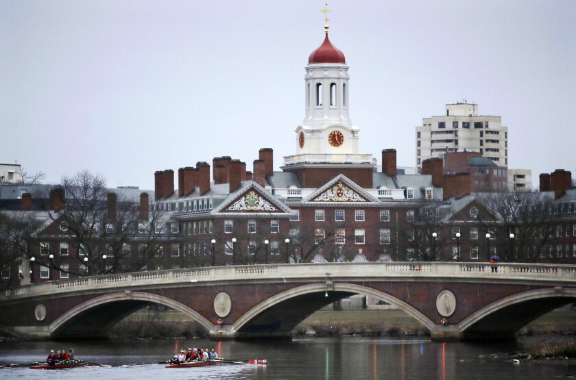 FILE - In this March 7, 2017, file photo, rowers paddle along the Charles River past the Harvard University campus in Cambridge, Mass. Harvard University will divest itself from holdings in fossil fuels. President Lawrence Bacow said Thursday, Sept. 9, 2021, that the university has legacy investments in a number of private equity funds with holdings in the fossil fuel industry and those indirect investments constitute less than 2% of the endowment. (AP Photo/Charles Krupa, File)