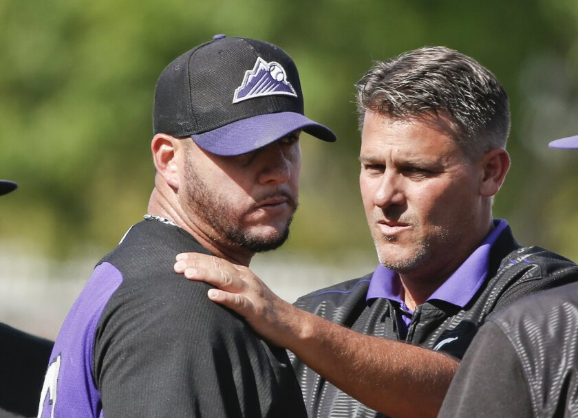 Colorado Rockies relief pitcher Rafael Betancourt is examined by trainer Keith Dugger after Betancourt was struck by a line drive while pitching against the Kansas City Royals in a spring training baseball game Thursday, March 19, 2015, in Surprise, Ariz.   Betancourt left the game.  (AP Photo/Lenn