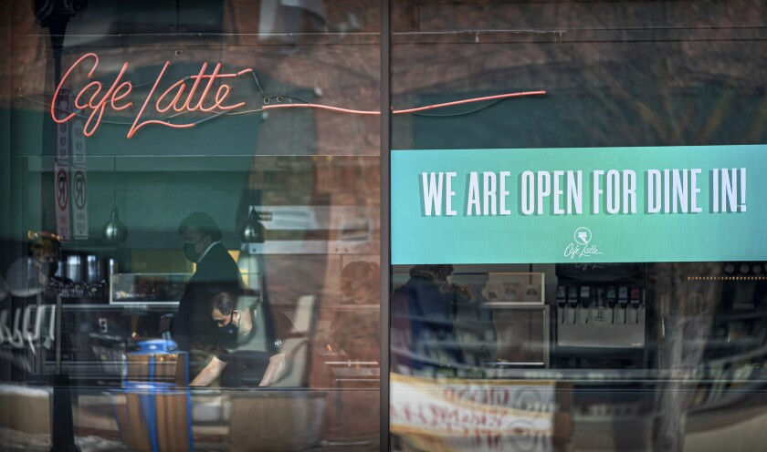 Cafe Latte on Grand Avenue, St. Paul had a sign in the window welcoming Dine In customers, on the first day of the new regulations, Monday, Jan. 11, 2021. (Glen Stubbe/Star Tribune via AP)