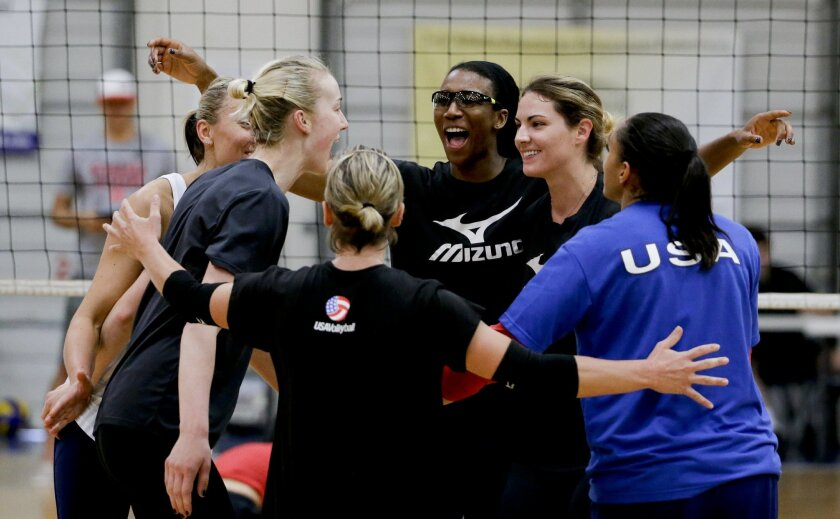 In this Tuesday, May 24, 2016, photo, U.S. women's national volleyball team players celebrate a point during practice in Anaheim, Calif. When the U.S. women's volleyball team got together months ago, the coaches embarked on a risky experiment: Evaluate your teammates. It paid off in a stronger squa