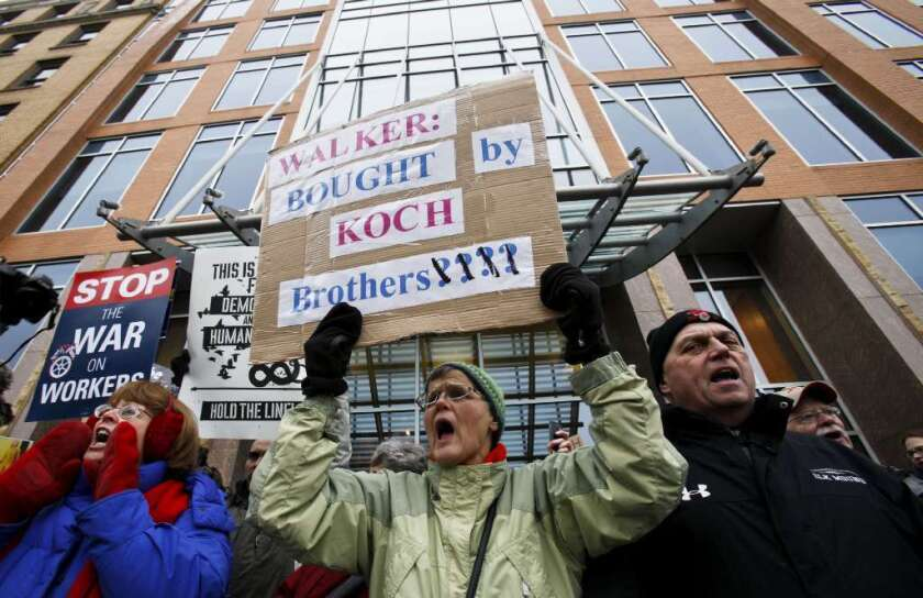 Jane Pederson, center, of Menomonie, Wis., protests in front of the offices of Koch Industries in Madison, Wis., in 2011.