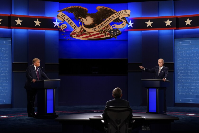 President Trump and former Vice President Joe Biden stand behind podiums on the debate stage.