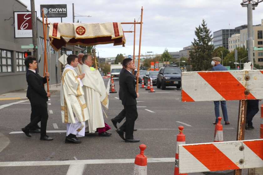 Archbishop Alexander Sample carries the Eucharist into downtown Portland, Ore., for an exorcism and rosary to bring peace and justice to the city on Oct. 17, 2020. In popular culture, exorcism often serves as a plot device in chilling films about demonic possession. Recently, two Roman Catholic archbishops showed a different face of exorcism. They performed the rite in well-attended outdoor ceremonies to drive out any evil spirits lingering after acrimonious protests. In Portland, Oregon, Archbishop Alexander Sample led a procession of more than 200 people to a city park, then conducted an exorcism rite. The event followed more than four months of racial-justice protests in Portland. (Ed Langlois/Catholic Sentinel via AP)