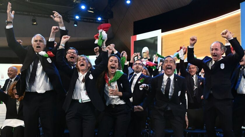 Members of the delegation from Milan/Cortina d'Ampezzo react Monday in Lausanne, Switzerland, after the Italian cities were announced as the host of the 2026 Winter Olympics.