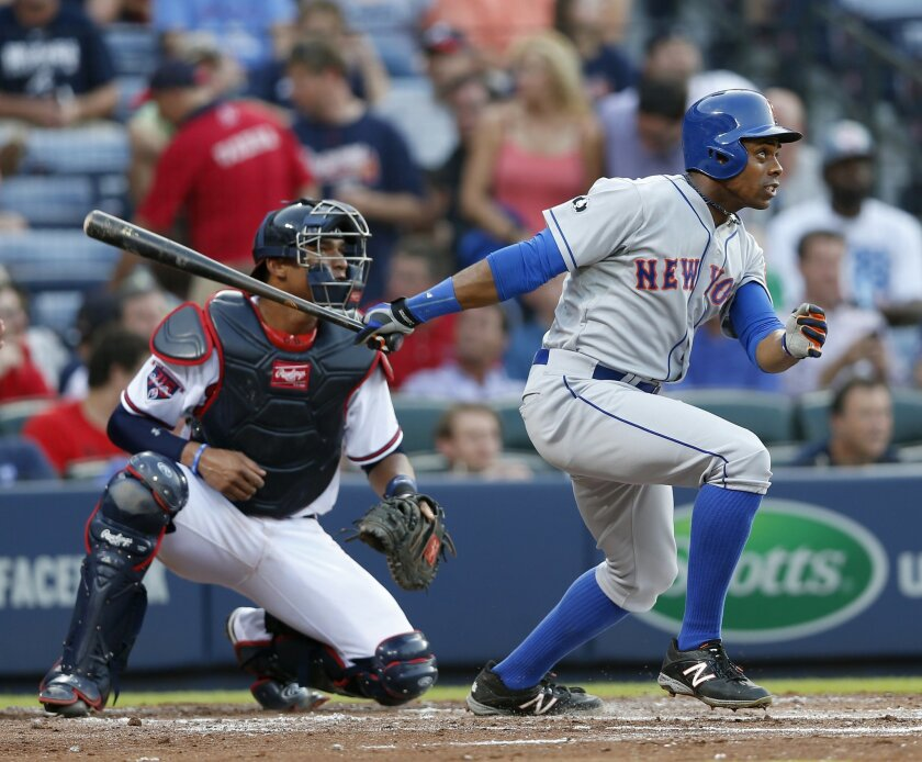 New York Mets' Curtis Granderson (3) follows through on a two-run home run as Atlanta Braves catcher Christian Bethancourt (25) looks on in the third inning of a baseball game in Atlanta, Tuesday, July 1, 2014.  (AP Photo/John Bazemore)