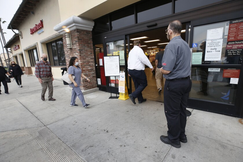 TORRANCE, CA - APRIL 27: Vons store supervisor Anthony Capone, right, greets shoppers as they are allowed in at 7 a.m. to the Vons located at 24325 Crenshaw Blvd in Torrance. Doors opened at 6 a.m. for seniors and at-risk shoppers due to the Coronavirus. Most of the team arrives at 5 a.m. to stock the shelves with product, sanitize the location for staff and shoppers, and picker/shoppers begin to collect items for .com home delivery shoppers. Vendors arriving throughout the morning must read a checklist of warnings, sign in and they must wear face covering. Vons on Monday, April 27, 2020 in Torrance, CA. (Al Seib / Los Angeles Times)