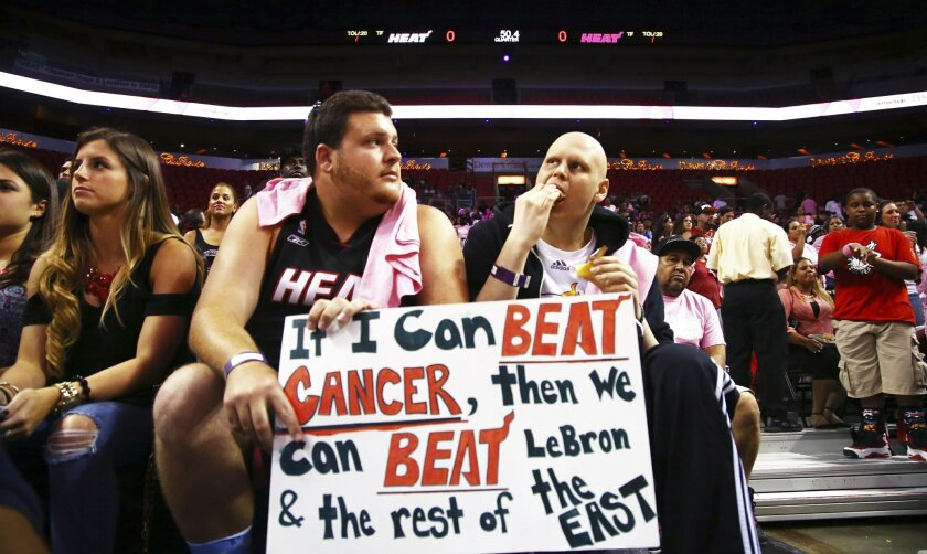 Two fans wait for the start of the Miami Heat's Red, White, and Pink basketball scrimmage Wednesday, Oct. 1, 2014, in Miami. (AP Photo/J Pat Carter)