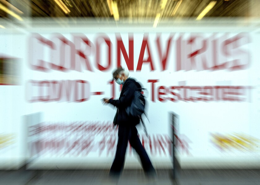 In this Feb.25, 2021 file photo a man walks by a sign in the window of a Coronavirus testing center in Frankfurt, Germany. (AP Photo/Michael Probst, file)