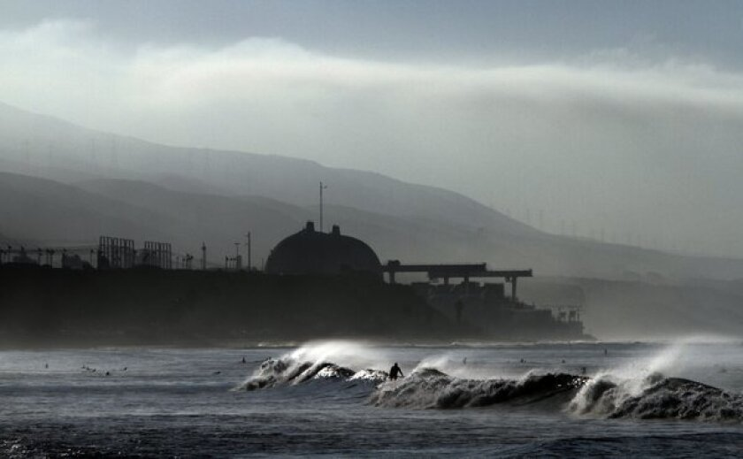 Surfers are out in the early morning with the San Onofre nuclear plant in the background.