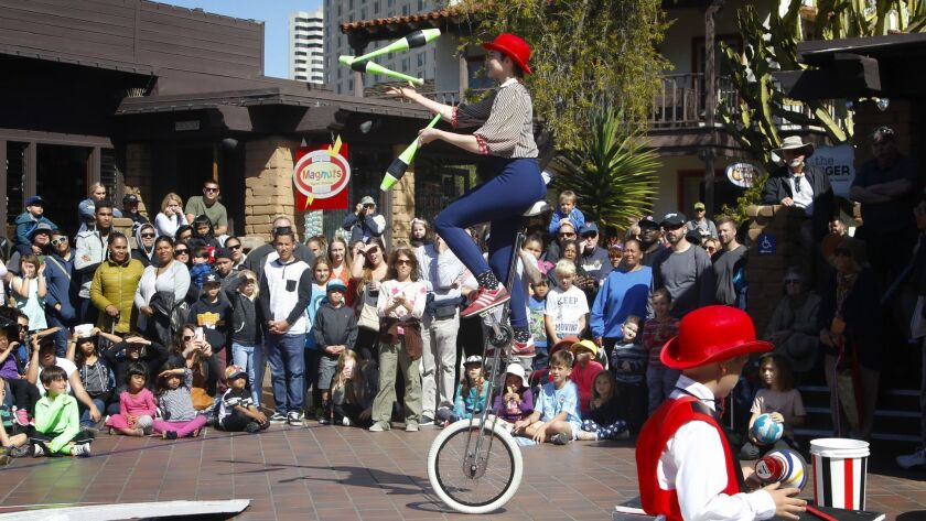Ananda Reilly with the Circus Mafia from San Diego performs on a unicycle while juggling for the crowd at Seaport Village Spring Festival.