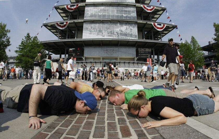 FILE - In this May 24, 2009, file photo, race fans lie down and kiss the yard of bricks at the Indianapolis Motor Speedway before the 93rd running of the Indianapolis 500 auto race in Indianapolis. The 100th running of the Indy 500 is Sunday, May 29, 2016. (AP Photo/Darron Cummings, File)