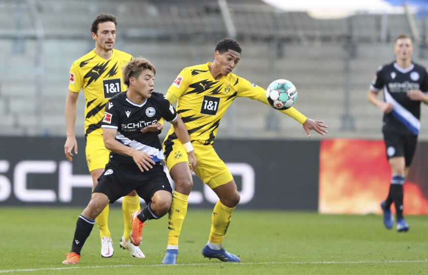 Bielefeld's Ritsu Doan, right, fights for the ball with Jude Bellingham, right, from Dortmund, during the German Bundesliga soccer match between Arminia Bielefeld and Borussia Dortmund in Bielefeld, Germany, Saturday, Oct. 31, 2020. (Friso Gentsch/dpa via AP)