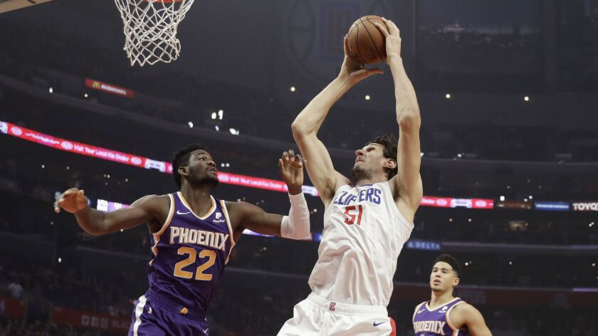 Clippers' Boban Marjanovic (51) grabs an offensive rebound over Phoenix Suns' Deandre Ayton (22) and puts it back in.