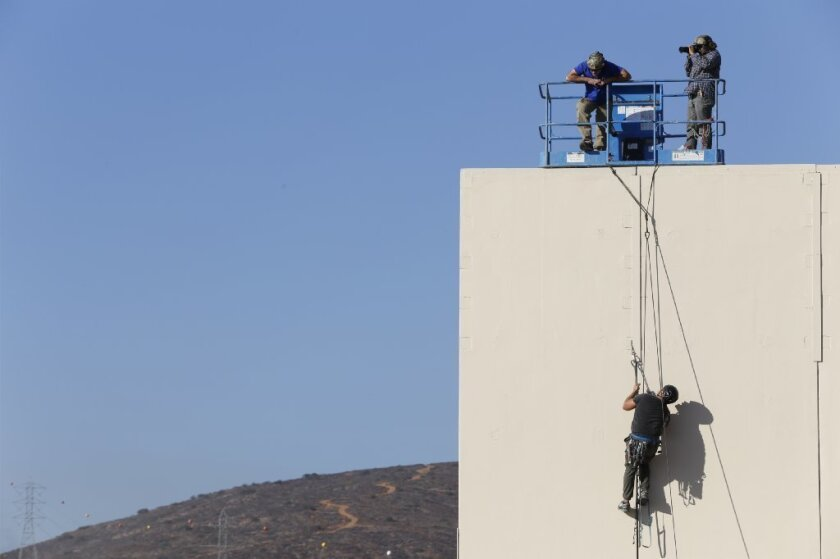Tijuana, Baja California, Mexico December 1st, 2017 | Testing the border wall prototypes. A climber moves up the wall. This entry is built by: Caddell Construction Co., (DE) LLC Montgomery Alabama. Concrete.