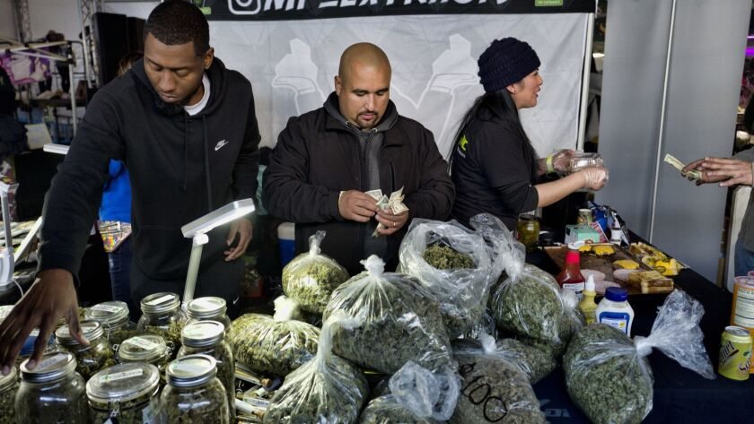 Vendors from MF Extracts count cash at their booth at a marijuana festival in Adelanto, Calif., in December.