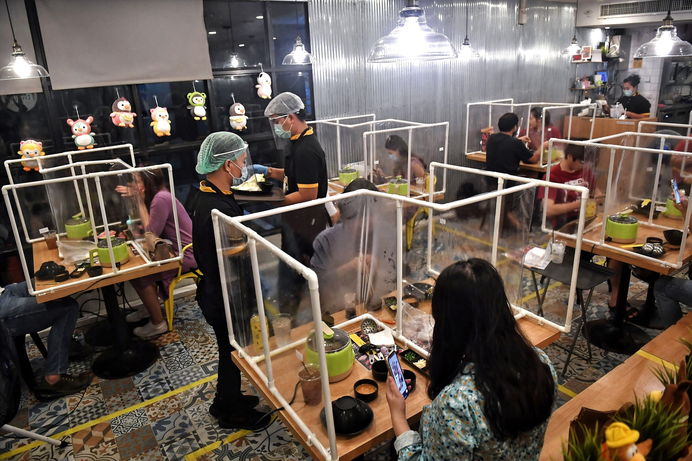 Plastic partitions separate diners on Tuesday in Bangkok.
