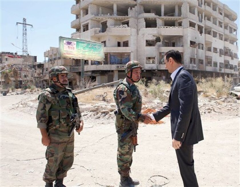 This image posted on the official Facebook page of the Syrian Presidency on Thursday, Aug. 1, 2013 purports to show Syrian President Bashar Assad shaking hands with a solider during Syrian Arab Army day in Darya, Syria. Syrian state-run TV says Assad has visited a tense Damascus suburb to inspect his troops on the occasion of the country's Army Day. The visit on Thursday is Assad's first known public trip outside the capital, his seat of power, since he visited the Baba Amr district in the centr