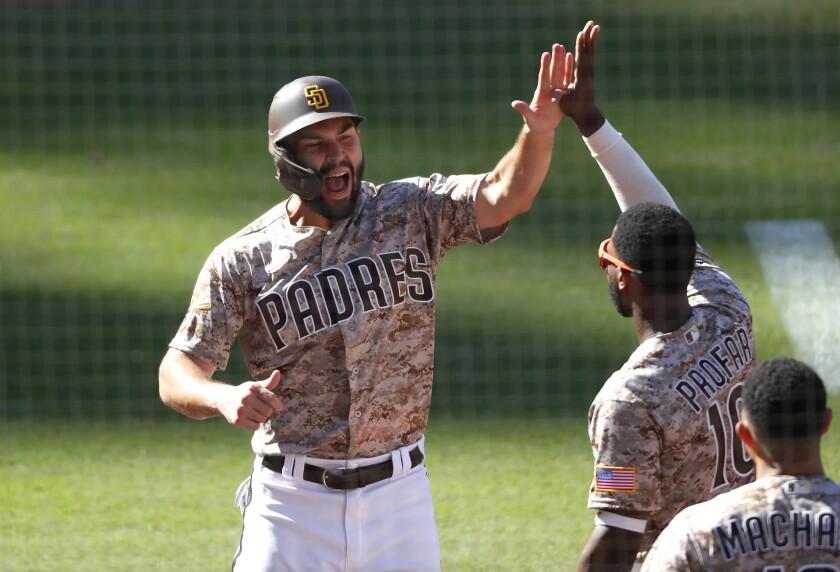 San Diego Padres' Eric Hosmer celebrates with Jurickson Profar after scoring.