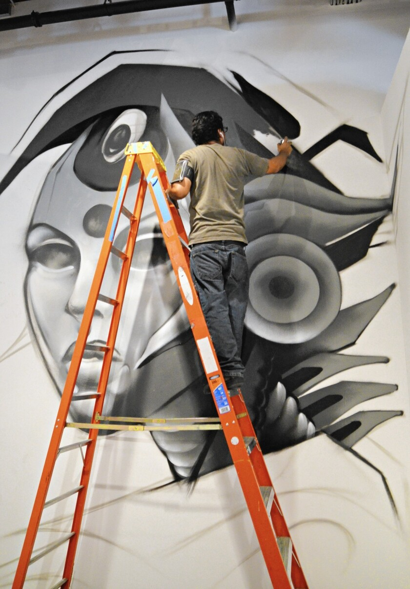 """Street artist Axayacatl Nevarez of Los Angeles spray-paints an image of a robot onto a wall at the Huntington Beach Art Center as part of the """"On the Wall"""" show, which opens Saturday."""