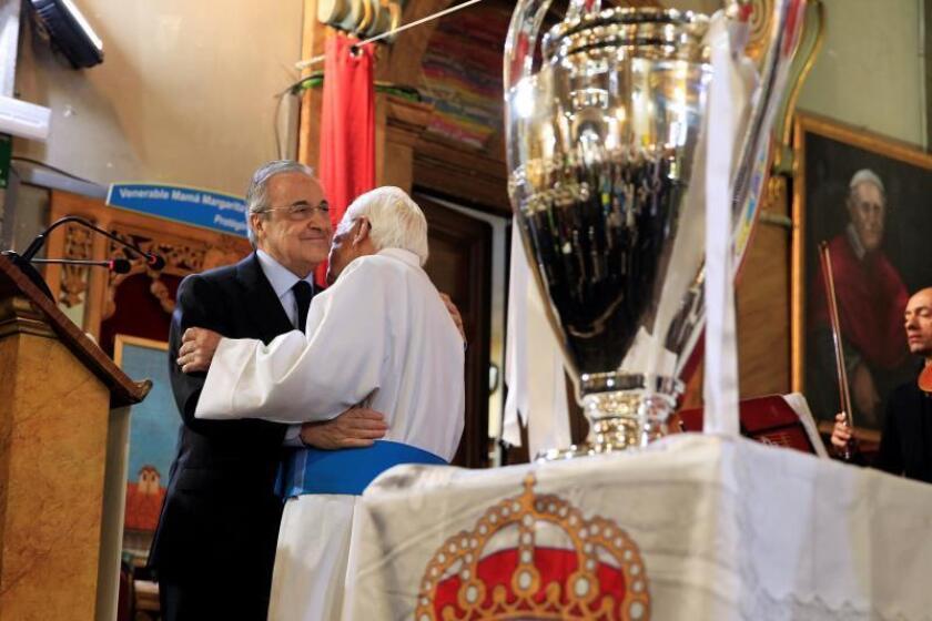El presidente del Real Madrid, Florentino Pérez (i), saluda al padre Ángel en su visita este jueves a la iglesia de San Antón, donde ha llevado el trofeo de la Liga de Campeones a los sin techo, que pidieron ver el trofeo de cerca. EFE
