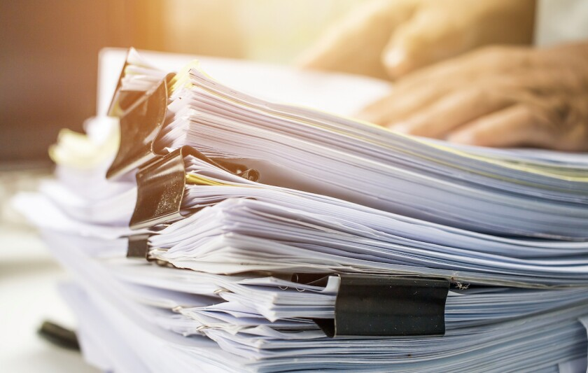 Businessman hands searching data information in Stack of papers