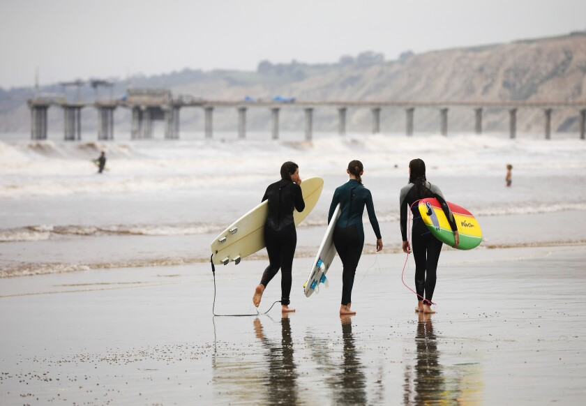 Three surfers in wetsuits carry surfboards on a beach