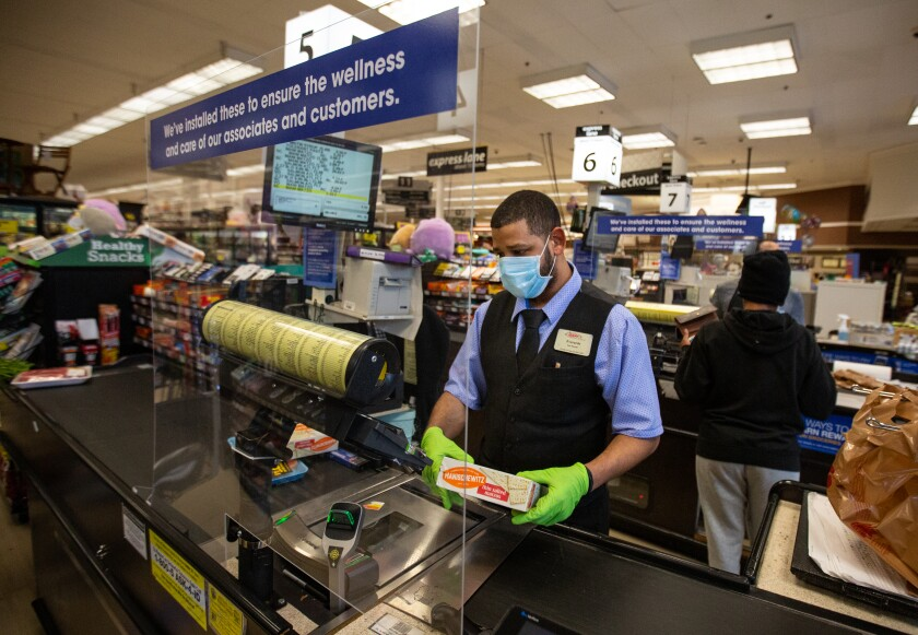 Everardo Gonzalez scans groceries behind a new plexiglass barrier at a Ralphs grocery store in Marina Del Rey during the coronavirus pandemic on Sunday.