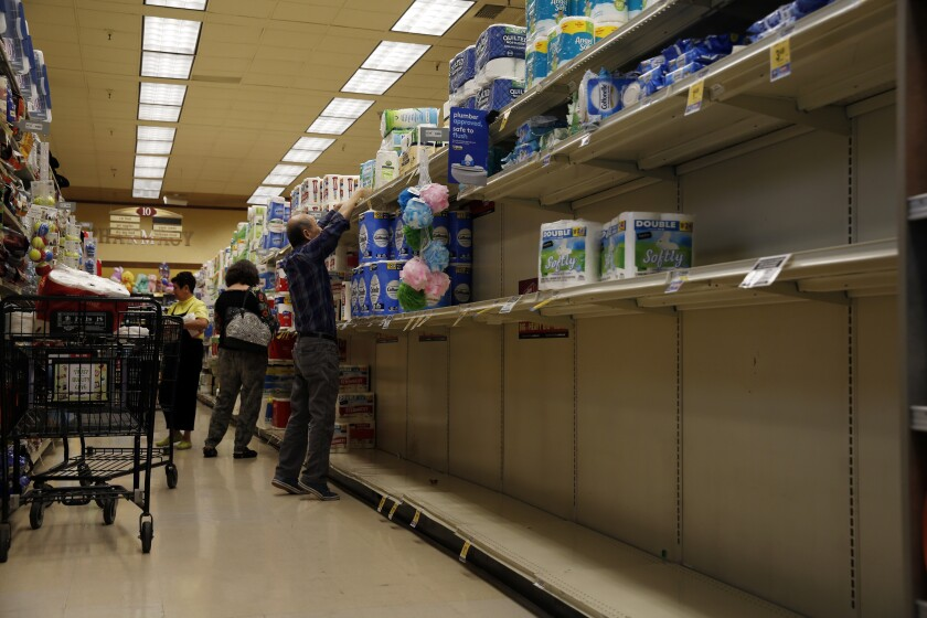 Shelves with toilet paper and disinfecting wipes are nearly empty at a Pavilions supermarket in South Pasadena on March 11.