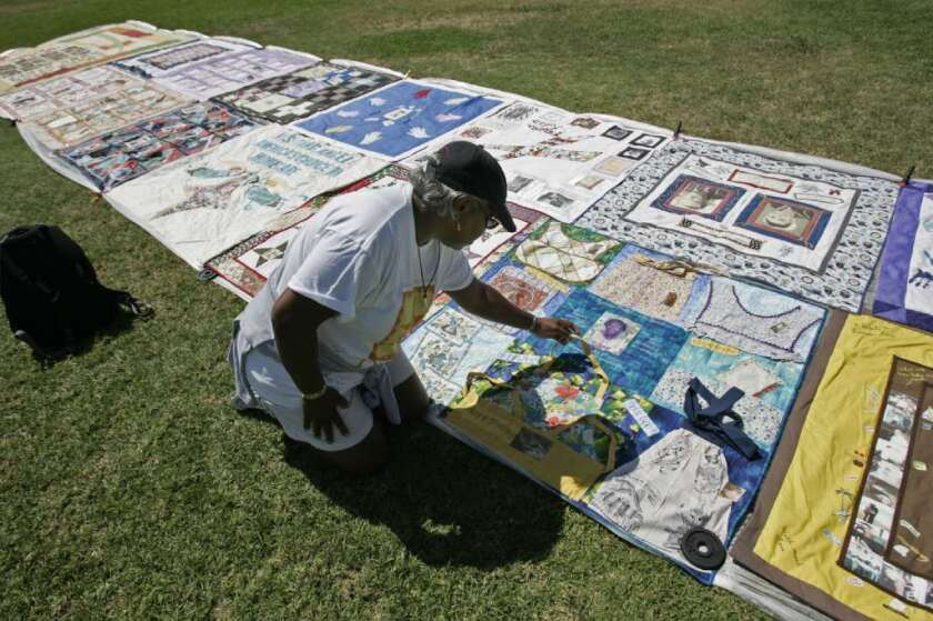 """The brains of those whose parents have been diagnosed with Alzheimer's disease show troubling hallmarks of the disease even in middle age, when their cognition is perfectly normal, a new study found. Here, a woman tends to the panel she made to commemorate her mother as part of the Alzheimer's Foundation of America's """"Quilt to Remember."""""""