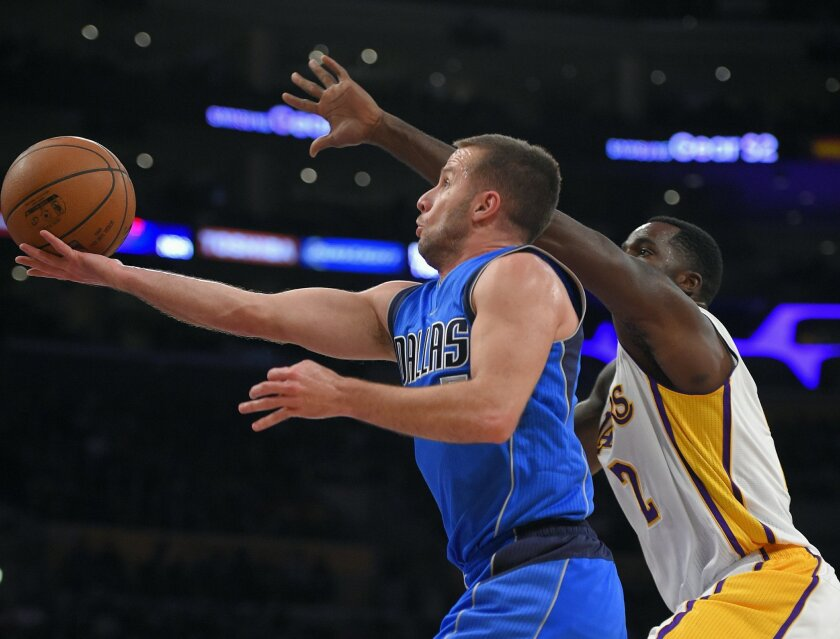 Dallas Mavericks guard J.J. Barea, left, shoots as Los Angeles Lakers forward Brandon Bass defends during the first half of an NBA basketball game, Sunday, Nov. 1, 2015, in Los Angeles. (AP Photo/Mark J. Terrill)