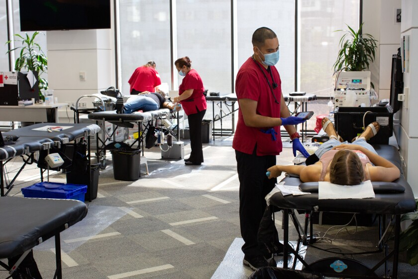Hugo Pena monitors Kendall McCrory as she donates blood during L.A. Care's blood drive in downtown Los Angeles.