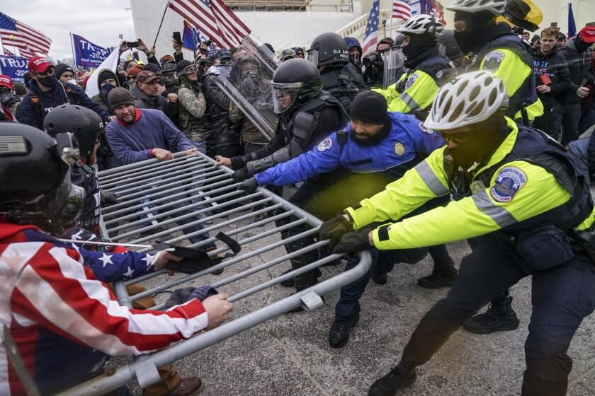 Trump supporters try to pull a piece of a barrier away from police.