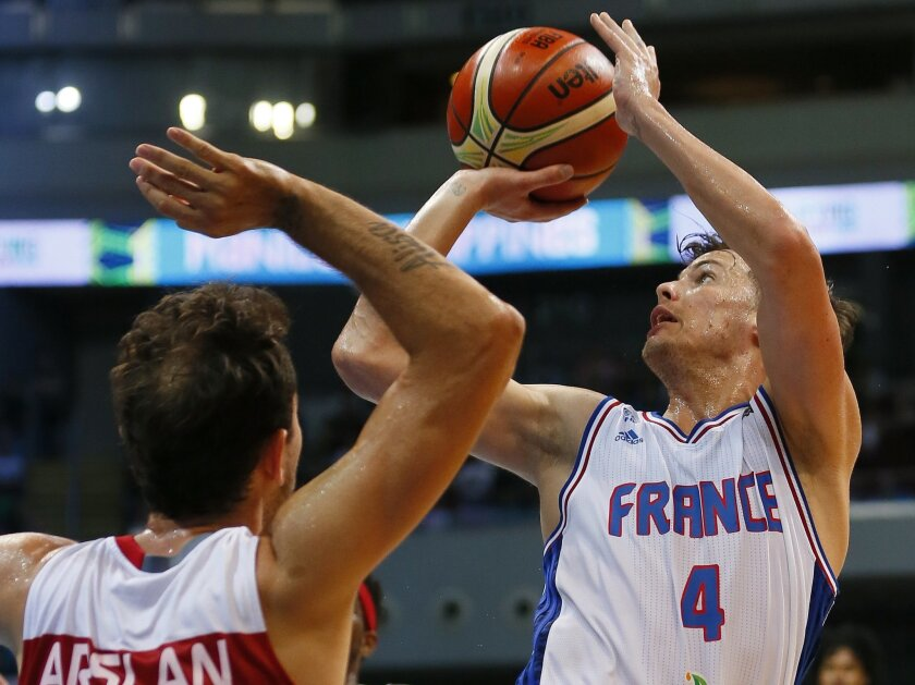 Thomas Heurtel of France, right, attempts to score over Turkey's Ender Arslan in the FIBA Olympic Qualifying basketball semi-final match Saturday, July 9, 2016 in suburban Pasay city south of Manila, Philippines. France won 75-63 to face Canada in the finals. (AP Photo/Bullit Marquez)