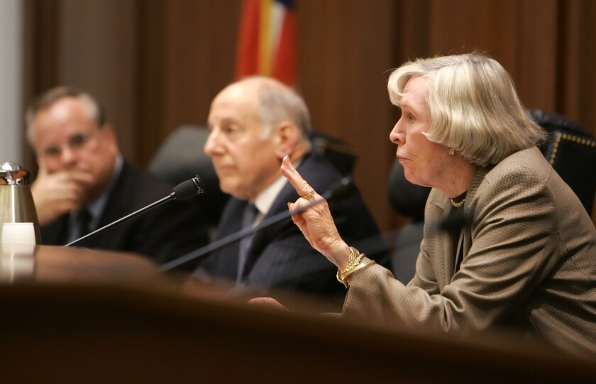 Judge Joan Dempsey Klein, with two men in the background, speaks into a microphone.