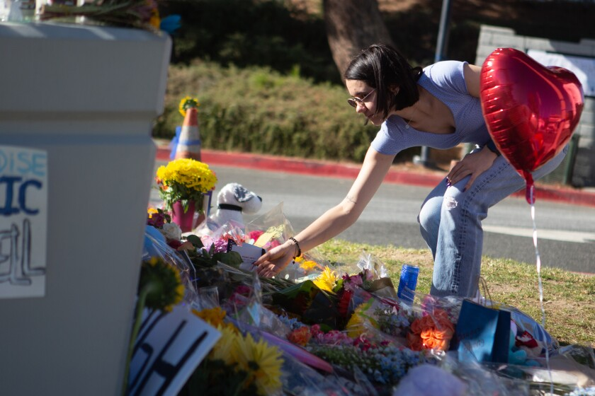 A mourner places flowers at a memorial for victims of the Nov. 14, 2019, Saugus High School shooting.