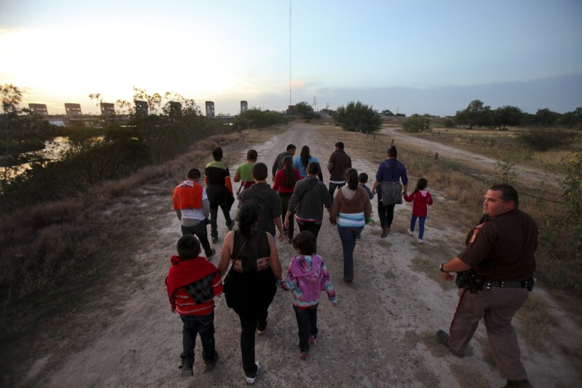 A Hidalgo County, Texas, deputy, right, guides a group of Guatemalan immigrants who crossed the border into the United States in 2014.
