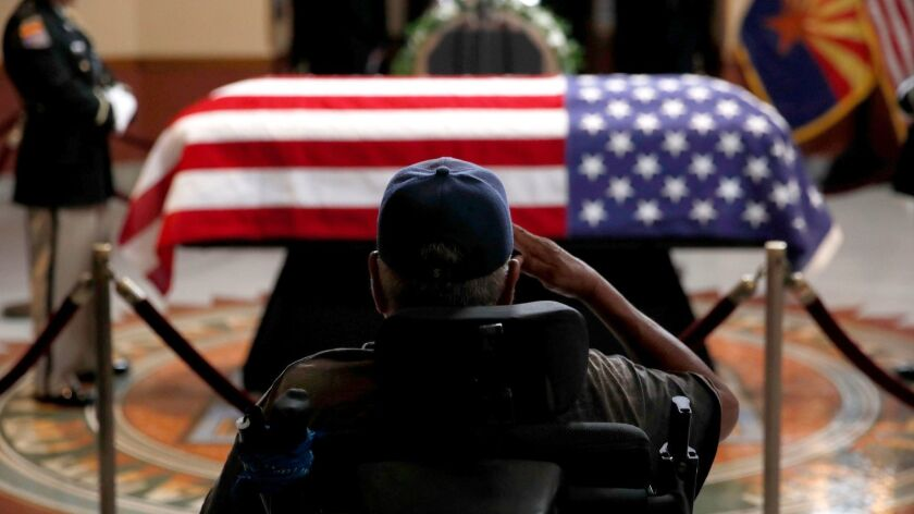 A veteran salutes the casket of Sen. John McCain at the Arizona state Capitol in Phoenix on Wednesday.