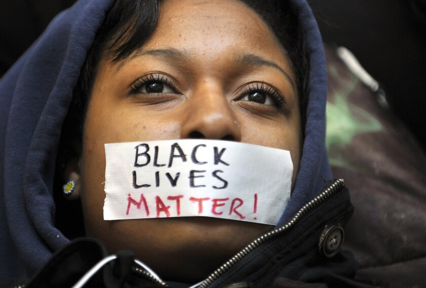 """Penn State student Zaniya Joe wears a piece of tape over her mouth that says """"Black Lives Matter."""""""