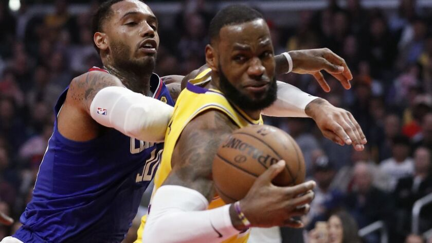 Lakers forward LeBron James spins to the basket against Clippers forward Mike Scott during the game Thursday night.